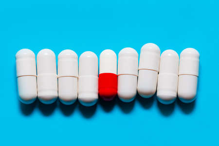 White Probiotic Capsules . One Red and White Capsule between White Capsules . Drugs at blue background . Pills in a row