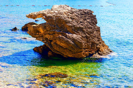 Coastal rock in the sea water . Exotic beach in the summer Stok Fotoğraf