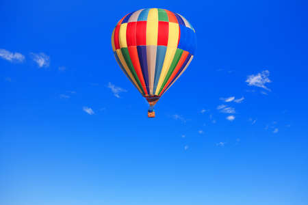 Hot air balloon in flight on the clear sky . Multi Colored air balloon . Traveling by air