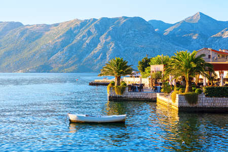 Coastal restaurant terrace at the tropical beach . Cafe terrace overlooking the Kotor Bay in Montenegro . Moored white boat Stok Fotoğraf