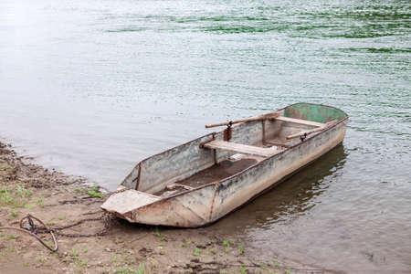 Moored rusty metal boat with oars . Fishing village