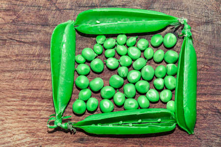 Green peas on the wooden table . Harvest of green peas