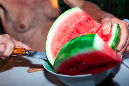 Cutting a watermelon with a knife . Farmer cuts slices of watermelon grown in his own garden