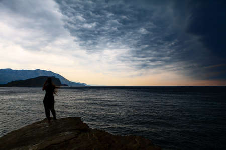 Girl standing on the seaside in the stormy weather and taking a pictures by smartphone . Altocumulus dark clouds over the sea