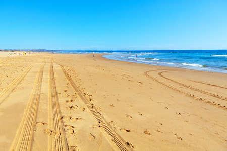 Atlantic Ocean Coastline in the Summer Day . Tractor prints on the sandy beach Stok Fotoğraf