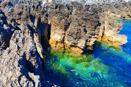 Coastal rock formation and ocean turquoise water . Tropical littoral . Oceanfront cliffs of Boca do Inferno Stok Fotoğraf