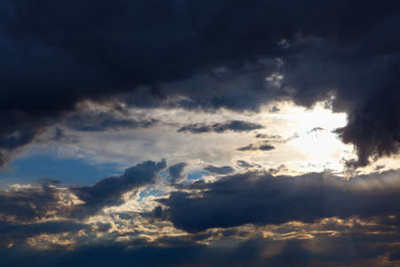 Sun shining through dark clouds . Sunlight rays and cloudy heaven
