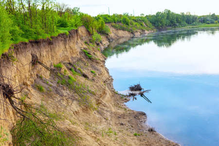 Riverside with clay cliff . Winding river scene . Exposed trees roots after a landslide Stok Fotoğraf
