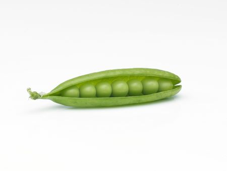 Seven peas in split open pod lying on side