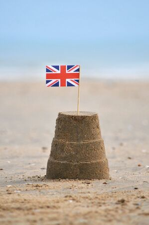 A sandcastle with a union jack flag on beach.