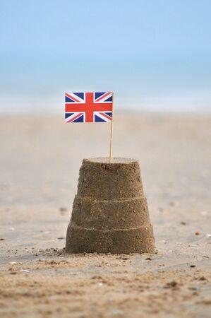 union beach: A sandcastle with a union jack flag on beach.