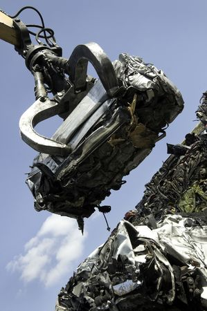 A scrap car being lifted by grab crane on to a pile of other scrapped cars. photo
