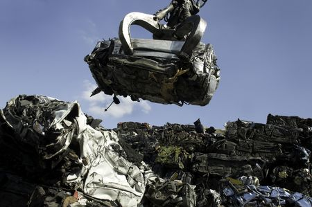 scrap heap: A crushed car being lifted on to pile of other crushed cars in scrap yard