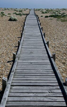 shingle: Wooden boardwalk across shingle to the horizon
