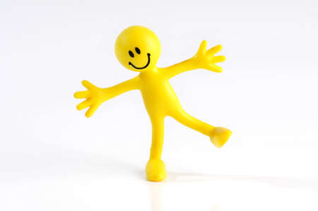 poise: A smiling yellow figure balancing on one leg arms outstreached on a white background