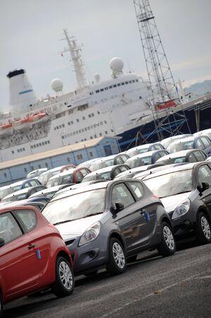 export and import: Una fila de coches nuevos importados en los puertos con buques de pasaje en el fondo Foto de archivo