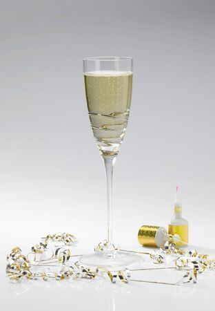 poppers: A single champagne flute on a white background wiht two party poppers and streamers