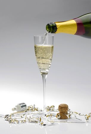 A single glass of champagne being poured from a bottle on a white background with popper and streamers photo