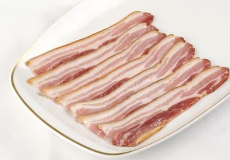 uncooked bacon: a white plate with strips of uncooked smoked streaky bacon