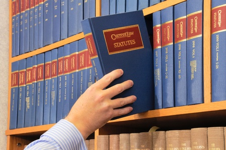 law: A red blue and gold law book being removed from a shelf by a male hand