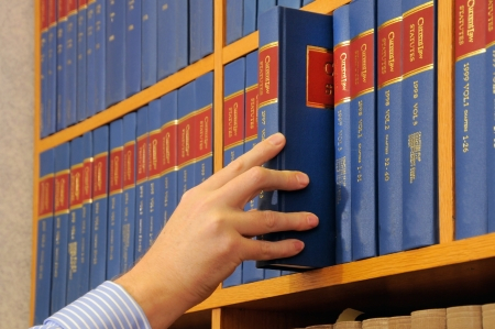 law library: A bookcase displaying a line of identical blue, red and gold books with hand removing or replacing a book