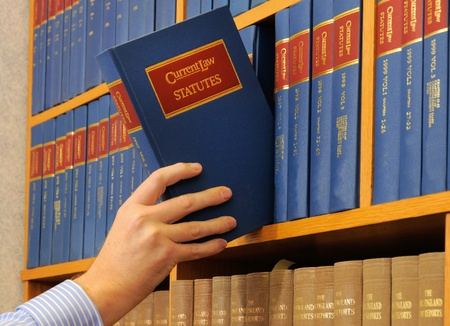 law books: A bookcase displaying a line of identical blue, red and gold books with hand removing or replacing a book