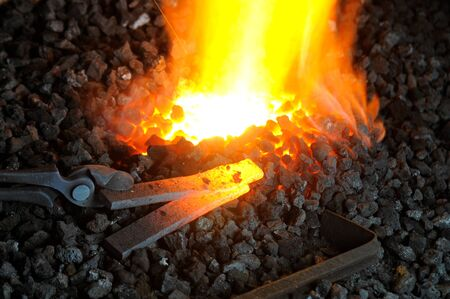 A pair of tongs gripping heated metal on glowing coal in forge Stock Photo - 10373623