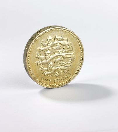 スターリング: 白い背景の上の端に立っているイギリスの 1 ポンド硬貨
