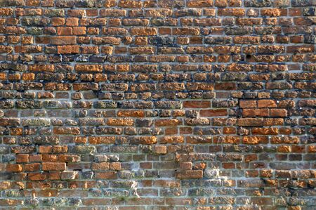 morter: an old red brick wall with damaged bricks and morter