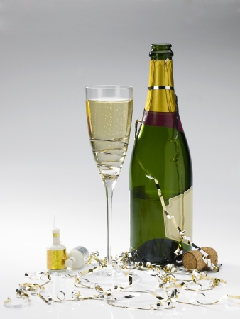 poppers: a champagne bottle, glass of champagne, streamers and poppers on a graduated grey background