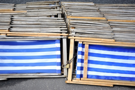 padlocked: Blue and white striped deckchairs stacked and padlocked togeather on the ground