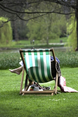 greeen: Seen fron behind a person relaxing in a greeen and white striped deckchair on grass in a park