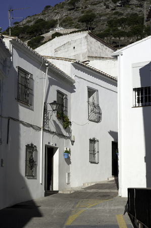 whitewashed: a view of a Spanish Andalucian village allyway with whitewashed houses and hill beyond Editorial