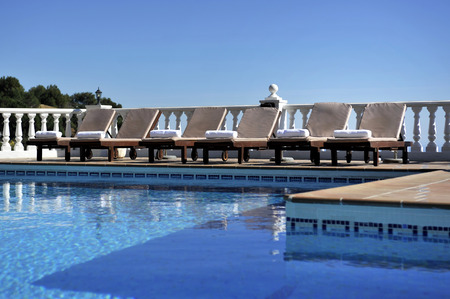 loungers: six sun loungers by the side of a swimming pool in the sun and blue sky