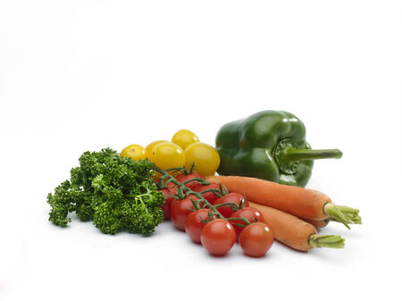veg: a selection of salad veg on a white background including carrots, peppers, parsley and red and yellow tomato Stock Photo