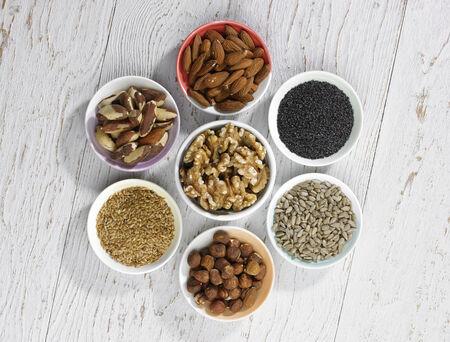intestinos: una selecci�n de cuatro tipos diferentes de frutos secos y tres tipos de semillas en los intestinos en un fondo de madera blanca