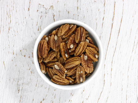 ingrediant: A bowl of Pecan nuts on a white wooden background
