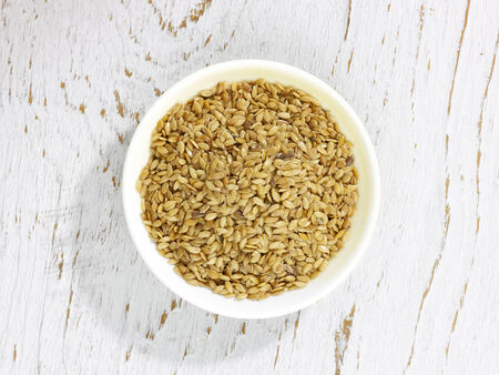 A bowl of seseme seeds on a white wooden background