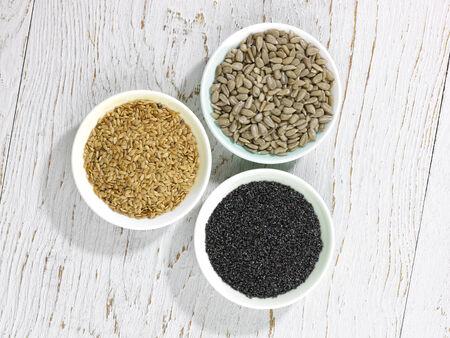 intestinos: tres tipos diferentes de semillas en los intestinos en una superficie de madera blanca Foto de archivo
