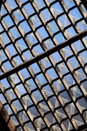rafters: a lattice pattend glass and wood roof with blue sky