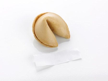 motto: a single unopened fortune cookie on a white background with blank paper motto in front