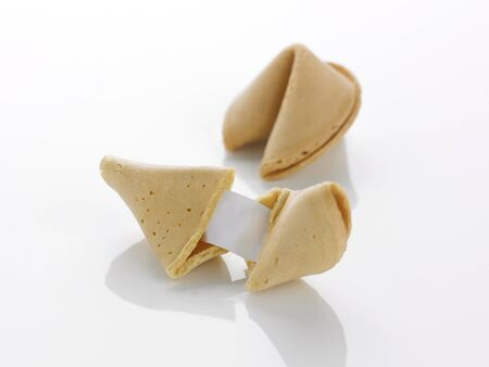 motto: two fortune cookies on a white background one opened showing a blank motto the other closed Stock Photo