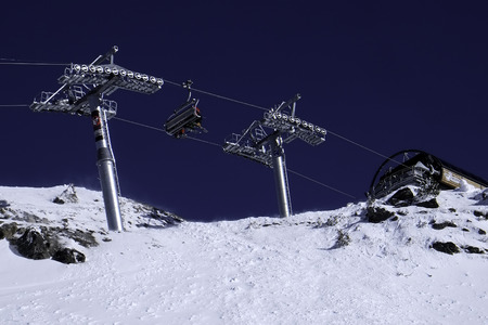 chair on the lift: View of ski chair lift carrying skiiers seen from below against a dark blue sky