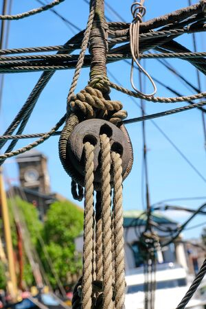 close up view of wooden sailing block and rigging on old sailboat