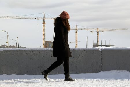 A girl in a hat and a black coat walks in the snow along a straight road against the background of multi-story buildings and construction cranes. Near the concrete fence