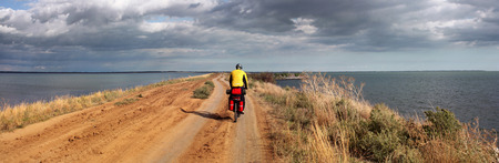 Tourist cyclist rides on a dirt road along the seashore horizontal banner