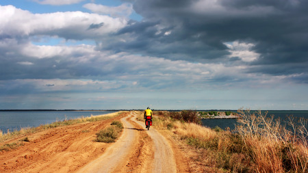 dirt road recreation: Tourist cyclist rides on a dirt road along the seashore Stock Photo