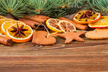 estrella de la vida: Dried oranges, star anise, cinnamon sticks and gingerbread on a wooden background -- Christmas still life background Foto de archivo