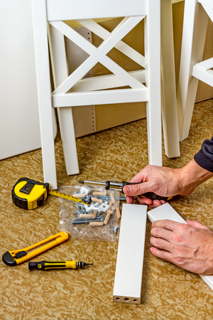 self assembly: Tools, instructions and details for self assembly furniture, man hands Stock Photo