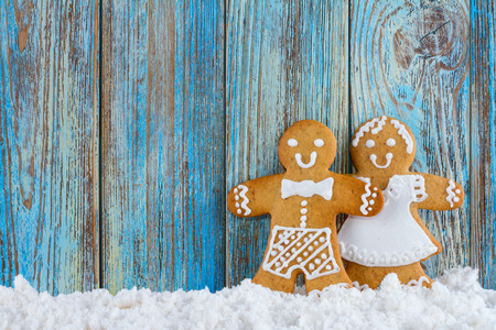 gingerbread man: Gingerbread cookies, gingerbread men in the snow on blue wooden background, Christmas or New Year background, template greeting card